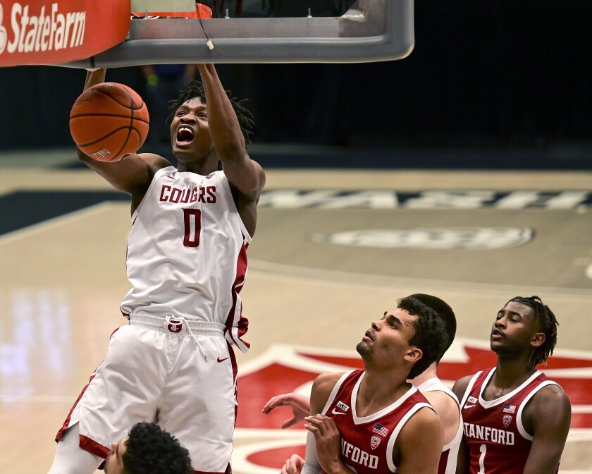 FILE - In this Saturday, Feb. 20, 2021 file photo, Washington State center Efe Abogidi, left, dunks the ball next to Stanford forward Oscar da Silva (13) during the first overtime of an NCAA college basketball game, in Pullman, Wash. A serious knee injury nearly ended Efe Abogidi's basketball career but he's now back on the NBA draft radar. The 19-year-old Nigerian is known for his high-flying dunks and plays for Washington State in the Pac-12. But his journey from West Africa to the West Coast was atypical with stops in Senegal and Australia. (AP Photo/Pete Caster, File)