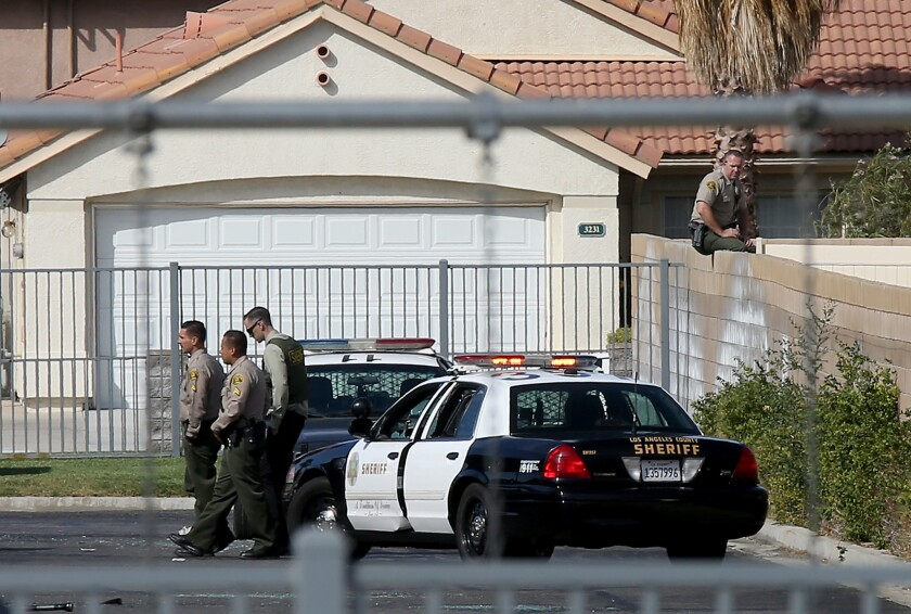 L.A. County sheriff's deputies stand near the fatal shooting scene in Lancaster on Wednesday afternoon.