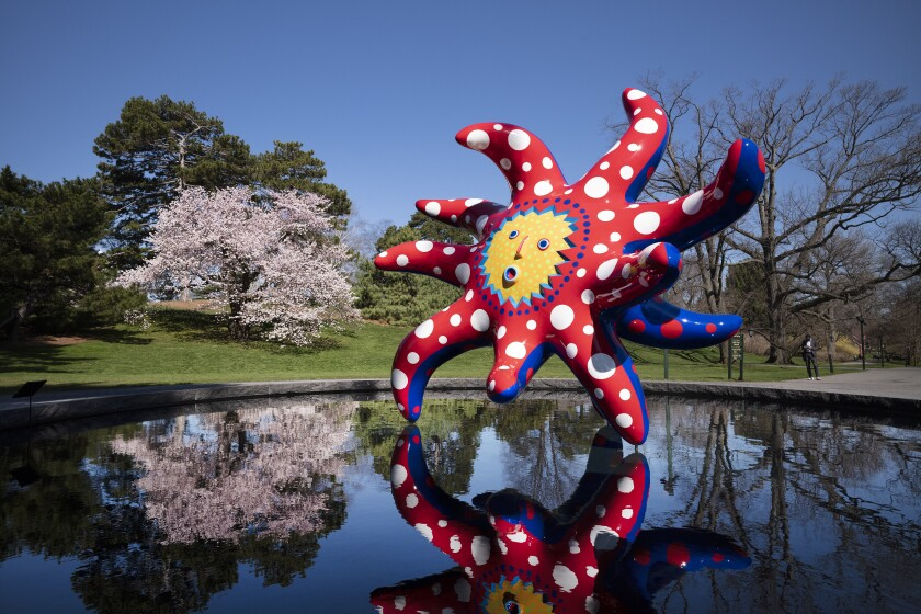 "The sculpture ""I Want to Fly to the Universe"" by Japanese artist Yayoi Kusama is reflected in a pool at the New York Botanical Garden, Thursday, April 8, 2021 in the Bronx borough of New York. The expansive exhibit has opened, and ticket sales have been brisk in a pandemic-weary city hungry for more outdoor cultural events. (AP Photo/Mark Lennihan)"