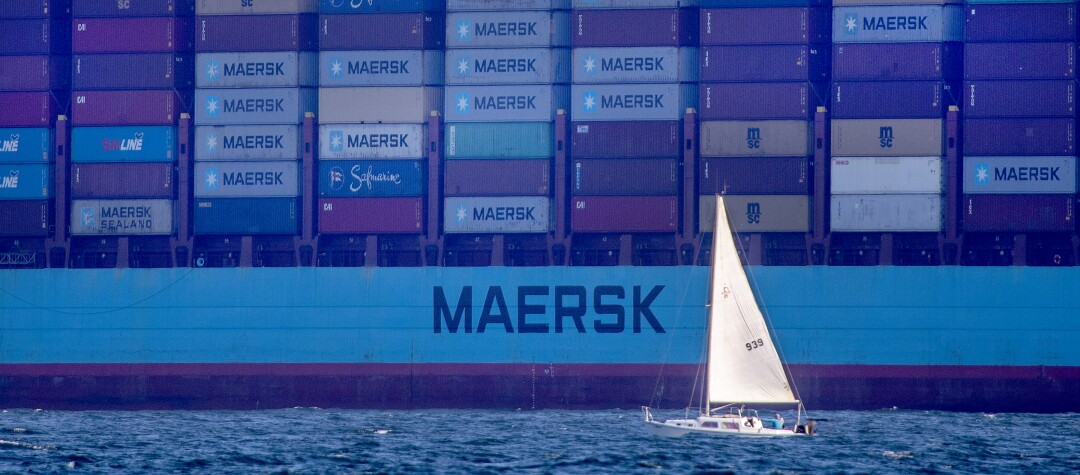 A sailboat passes one of the container ships sitting off the coast of the ports of Los Angeles and Long Beach.
