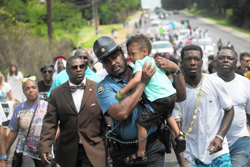 Capt. Ron Johnson of the Missouri Highway Patrol carries a demonstrator's child during a nearly five-mile march to mark the anniversary of Michael Brown's shooting death in Ferguson, Mo.