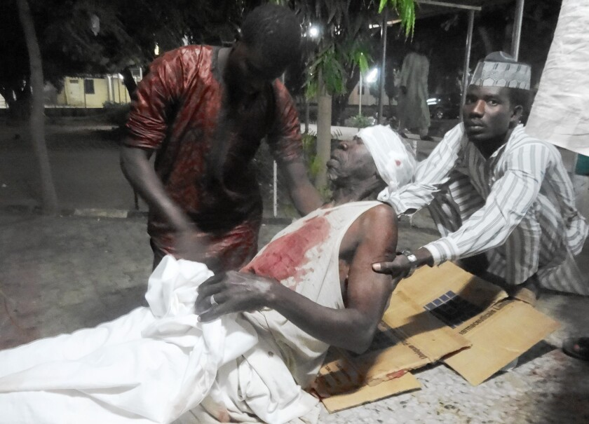 Men attend to their father in an emergency room after a suicide attack at a mosque in Kano, Nigeria, that killed more than 100 people in November 2014.