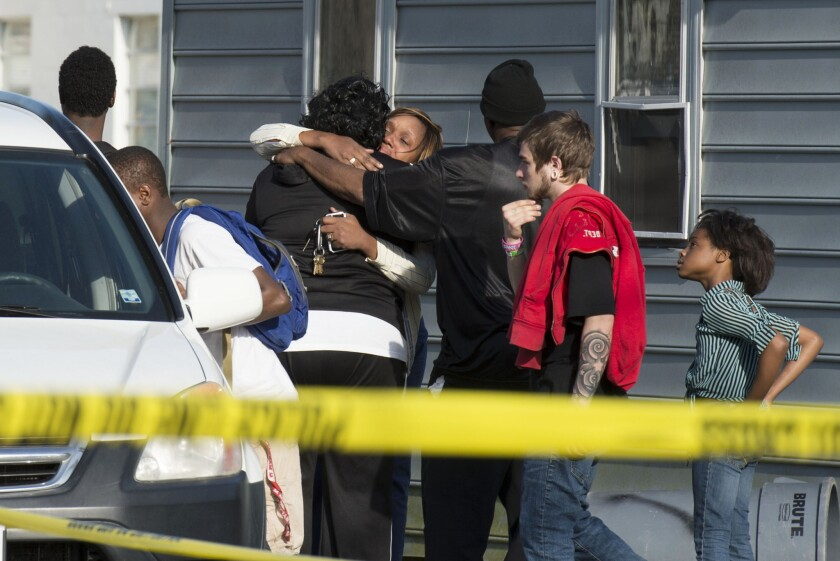 People gather outside a house where police say seven children and one adult were found dead Monday.