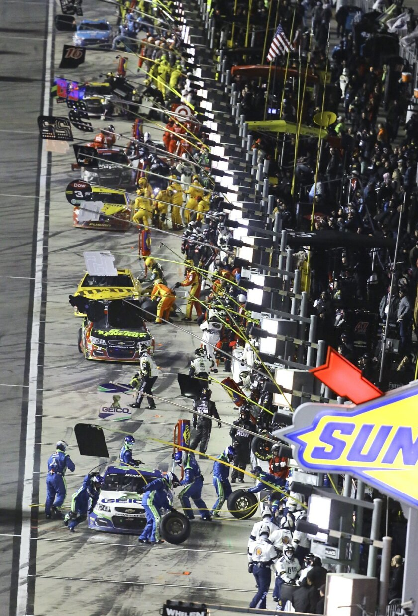Cars line the pit road as drivers stop for fuel and tires during the Sprint Unlimited auto race at Daytona International Speedway, Saturday, Feb. 13, 2016, in Daytona Beach, Fla. (AP Photo/David Graham)