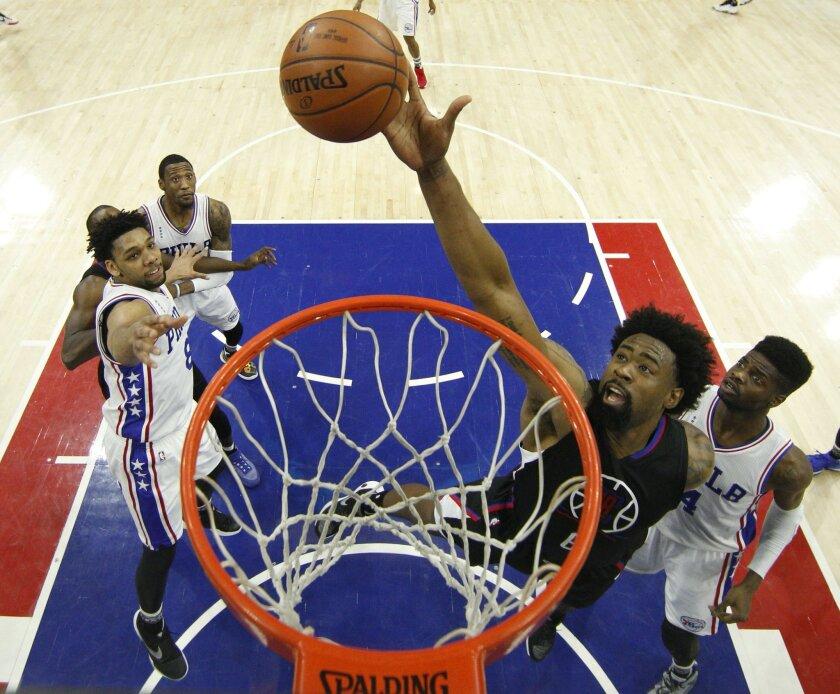 DeAndre Jordan (6) de los Clippers de Los Angeles trata de anotar en medio de Nerlens Noel (4) y Jahlil Okafor (8) de los 76ers de Filadelfia el lunes 8 de febrero de 2016. (AP Foto/Chris Szagola)