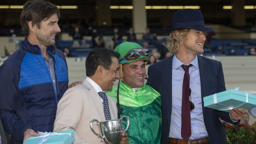 In a photo provided by Benoit Photo, brothers Luke Wilson, left, and Owen Wilson smile with jockeys