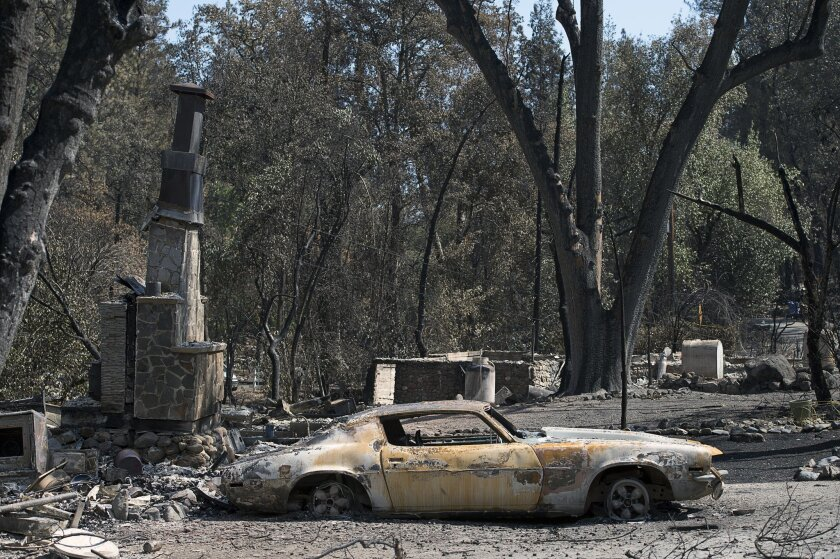 Scorched trees and burned vehicles and the remains of homes cover the landscape Thursday Sept. 17, 2015, in Anderson Springs, Calif. The Valley fire that sped through Middletown and other parts of rural Lake County, less than 100 miles north of San Francisco, has continued to burn since Saturday de
