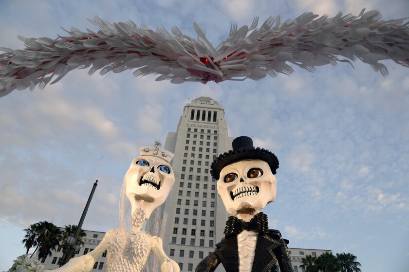 A 'Dia de los Muertos' (Day of the Dead) altar featuring a wedding couple created by Marcus Politz is displayed in front of City Hall in downtown Los Angeles.