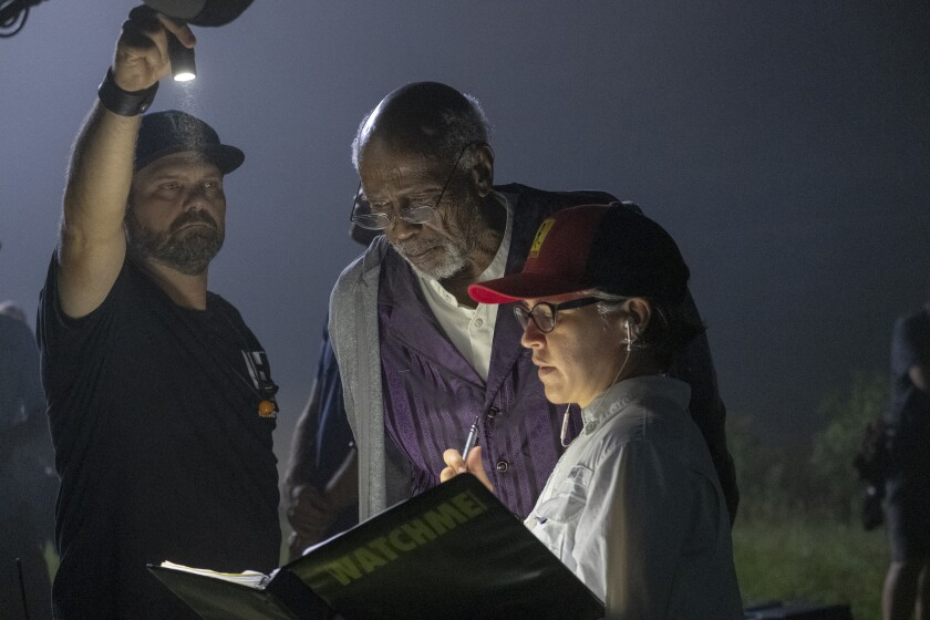 "Louis Gossett Jr. and Nicole Kassell look at a binder she's holding with ""WATCHMEN"" on the cover while another man shines a flashlight."