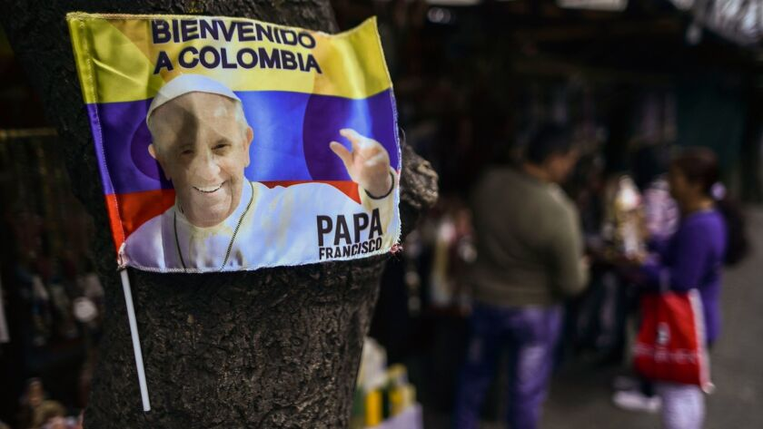 Pope Francis, who is to arrive in Colombia on Wednesday, is seen on a flag in Bogota.