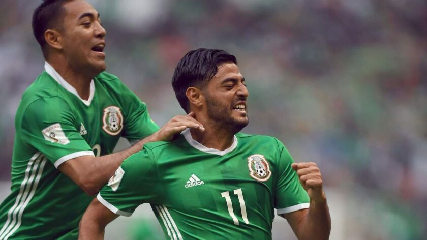 Mexico's forward Carlos Vela, right, celebrates with teammate Marco Fabian after scoring against the U.S. during their 2018 World Cup CONCACAF qualifier match, in Mexico City on June 11, 2017.