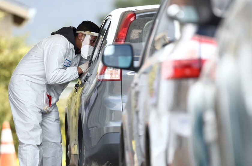 A medical professional administers a coronavirus test at a drive-through location run by staffers from University of California, San Francisco Medical Center (UCSF) in the parking lot of the Bolinas Fire Department.