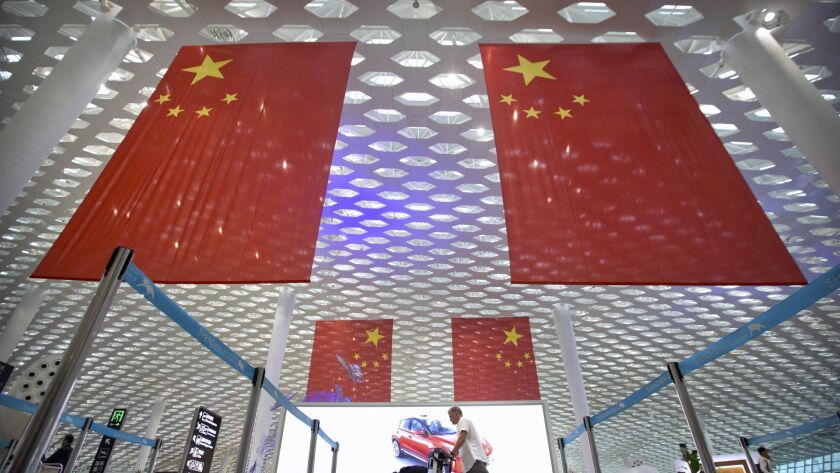 A traveler pushes his luggage beneath large Chinese flags on hanging from the ceiling in Shenzhen Ba