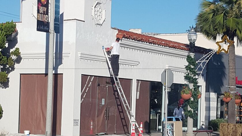 Signage for the Reebok store at the corner of Girard Avenue and Silverado Street is removed after it closed at the end of 2016.
