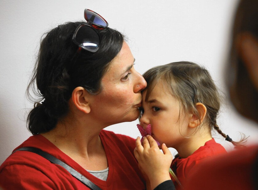 Jessica Damon kisses her daughter, Lucinda Mendes, after leaving a committee hearing where lawmakers approved a measure requiring California schoolchildren to get vaccinated.