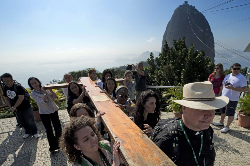 Ahead of Pope Francis' visit, Roman Catholics carry the World Youth Day cross up Sugarloaf Mountain in Rio de Janeiro.