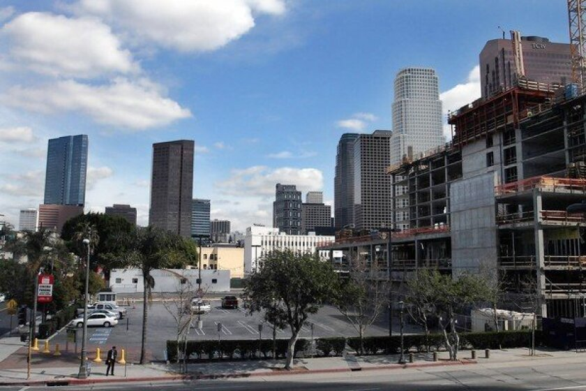 The Renaissance Hotel will rise in downtown L.A. on Olympic Boulevard, on the site of a parking lot, left. To the right, work continues on a 24-story tower already under construction that will house a Courtyard by Marriott and a Residence Inn by Marriott under one roof.