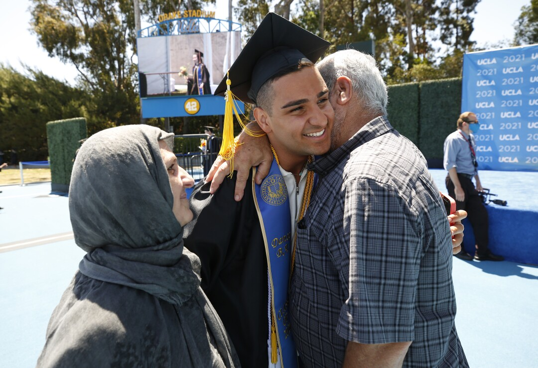 Paywand Baghal, graduating with a degree in Dance and Biology hugs his parents