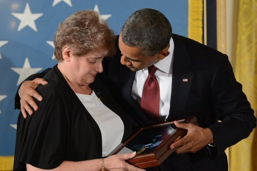 President Obama hugs Rose Mary Sabo-Brown, widow of Army Spc. Leslie H. Sabo, at the Medal of Honor ceremony in the East Room of the White House.