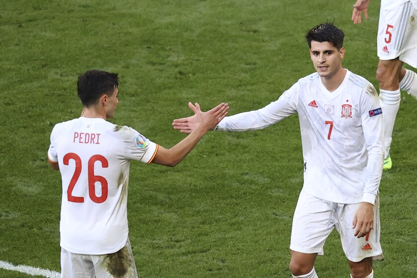 Spain's Alvaro Morata celebrates with his teammate Pedri after scoring his team's fourth goal during the Euro 2020 soccer championship round of 16 match between Croatia and Spain, at Parken stadium in Copenhagen, Denmark, Monday, June 28, 2021. (Wolfgang Rattay, Pool via AP)