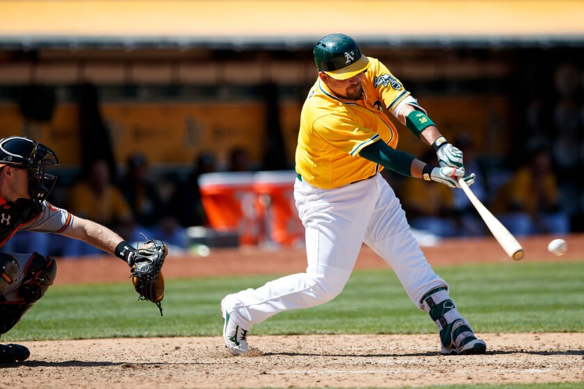 Athletics slugger Billy Butler (16) hits an RBI single against the Baltimore Orioles during the eighth inning on Aug. 11.