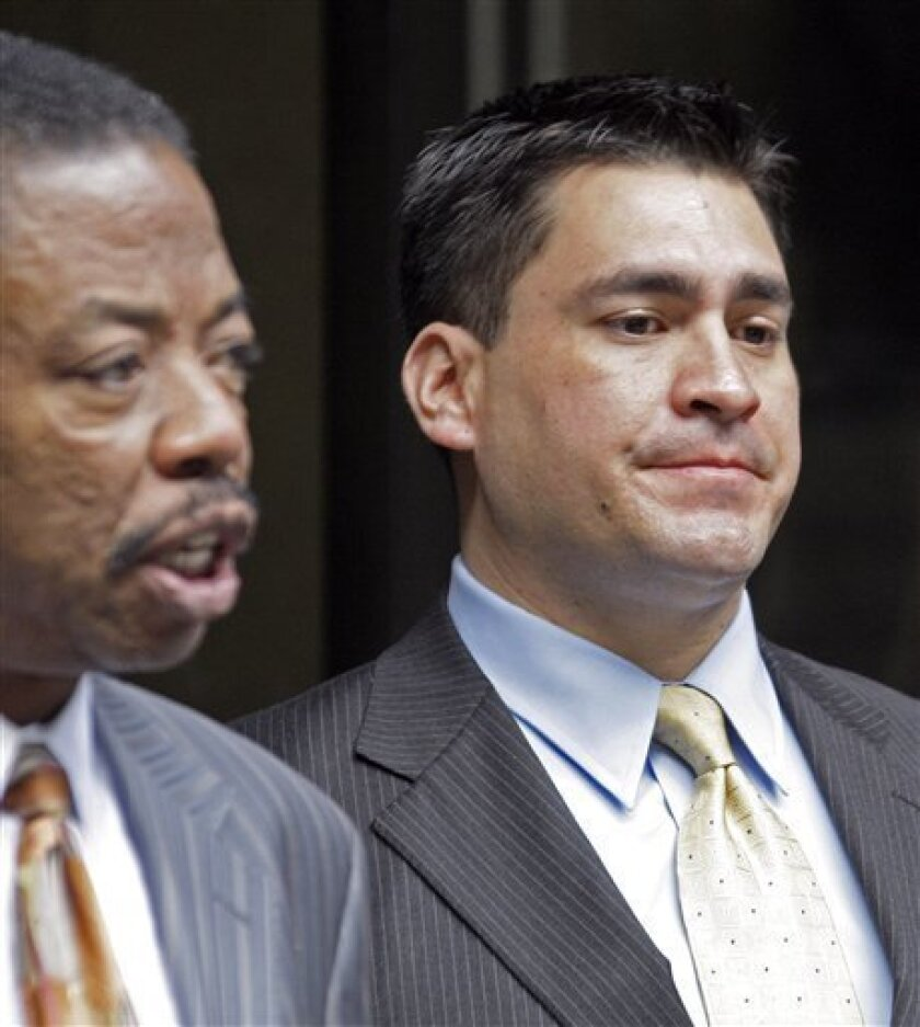 Security guard Alberto Alvarez, right, listens as his attorney Carl Douglas talks to reporters as they leave the preliminary hearing for Michael Jackson's doctor Conrad Murray who is charged in the death of the singer, at Los Angeles Superior Court, Wednesday, Jan. 5, 2011. (AP Photo/Reed Saxon)
