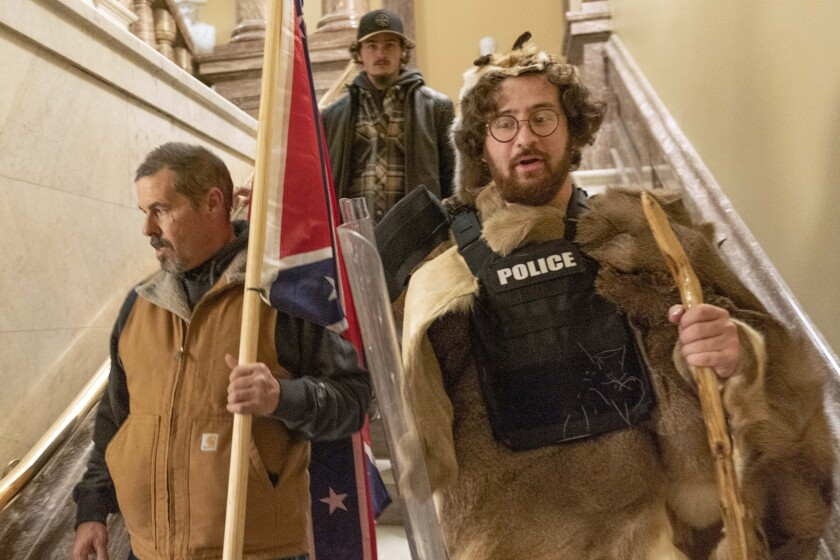 A man with a Confederate flag and another dressed in fur and using a walking stick descend a staircase.