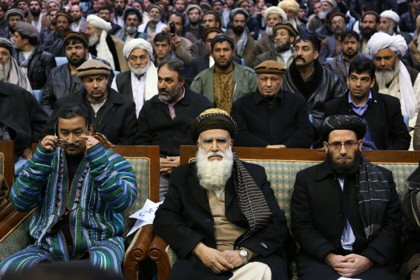 Afghan presidential candidate and former warlord Abdul Rab Rasoul Sayyaf, center, attends a campaign rally in Kabul, Afghanistan, Thursday, Feb. 6, 2014. Sayyaf, who has been accused of war crimes and atrocities during the 1990s, appeared before thousands of supporters in Kabul on Thursday and laid out a vision for Afghanistan's future that bore striking similarities to the policy platforms of many of the more moderate presidential hopefuls in the field of 11 vying to succeed President Hamid Karzai. (AP Photo/Rahmat Gul)