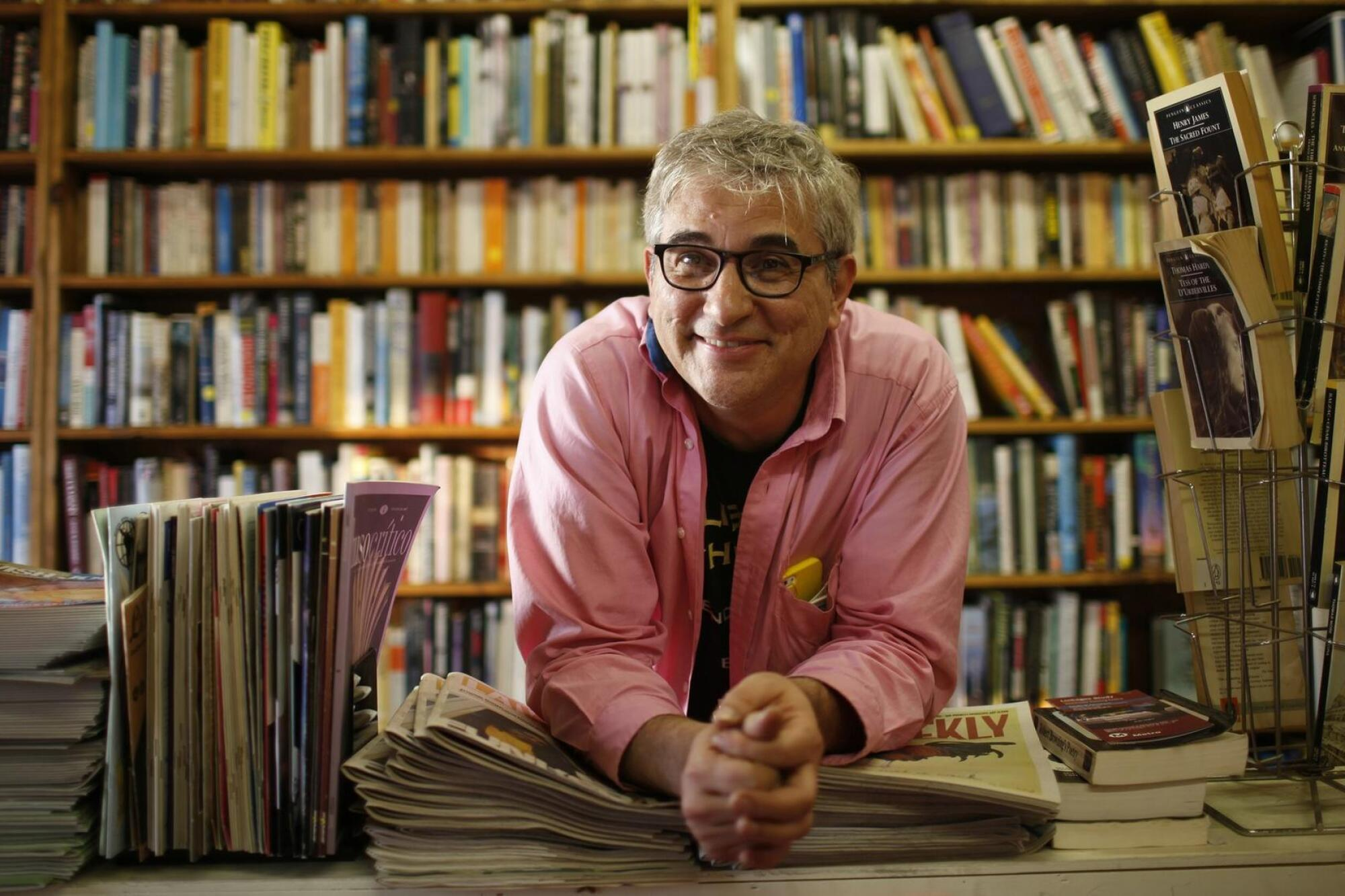 David Kipen leans on a stack of publications on a table with shelves of books in the background.