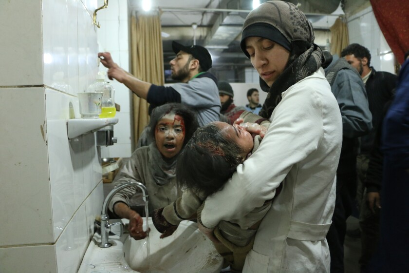 "In Ghouta, Syria,  a doctor treats an injured baby  in a crowded operating room in a scene from ""The Cave."""