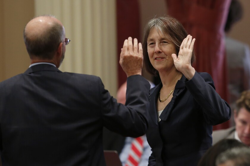 State Sen. Nancy Skinner (D-Berkeley) and Sen. Steven Glazer (D-Orinda) slap palms in celebration after her measure to let athletes at California colleges hire agents and sign endorsement deals was approved by the Senate on Sept. 11.