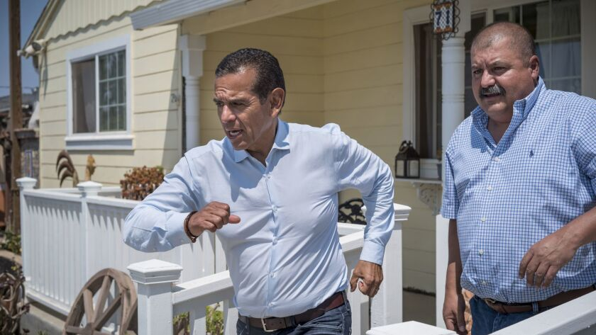 Antonio Villaraigosa dashes toward his car after visiting the Salinas home of harvester Ricky Cabrer