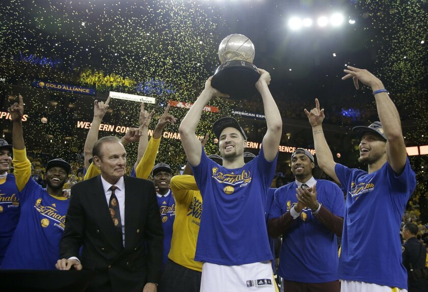 Former NBA player Rick Barry, center left, watches as Golden State Warriors guard Klay Thompson, center, Stephen Curry, right, and their teammates celebrate after beating the Oklahoma City Thunder in Game 7 of the NBA basketball Western Conference finals in Oakland, Calif., Monday, May 30, 2016. Th
