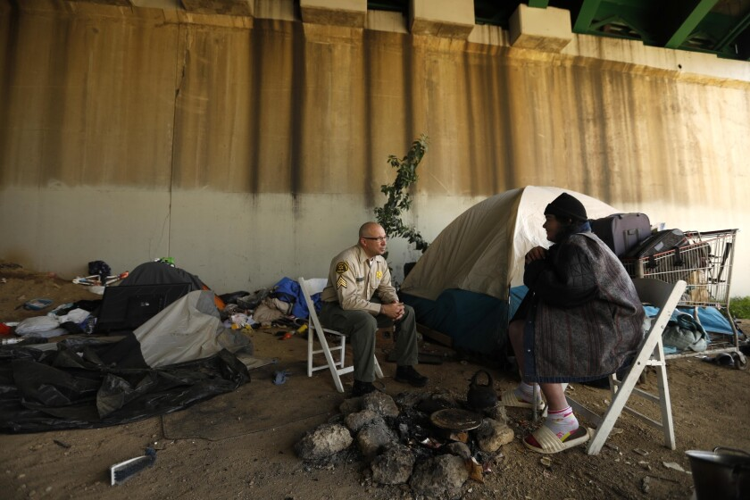 Sheriff Deputy Sgt. William Kitchin talks with Leah Davalos under an overpass while she was recorded for the 2019 Greater Los Angeles Homeless Count in the City of Commerce.