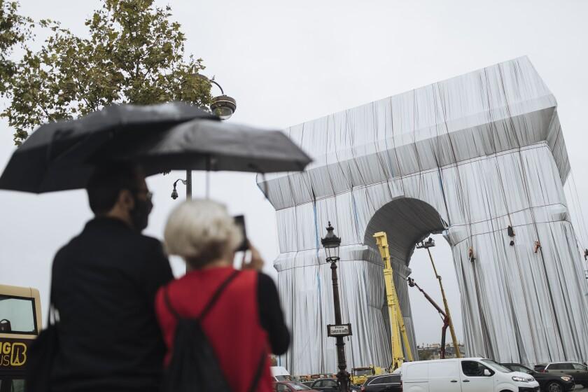 Dos personas miran cómo varios trabajadores envuelven en tela el monumento del Arco de Triunfo,
