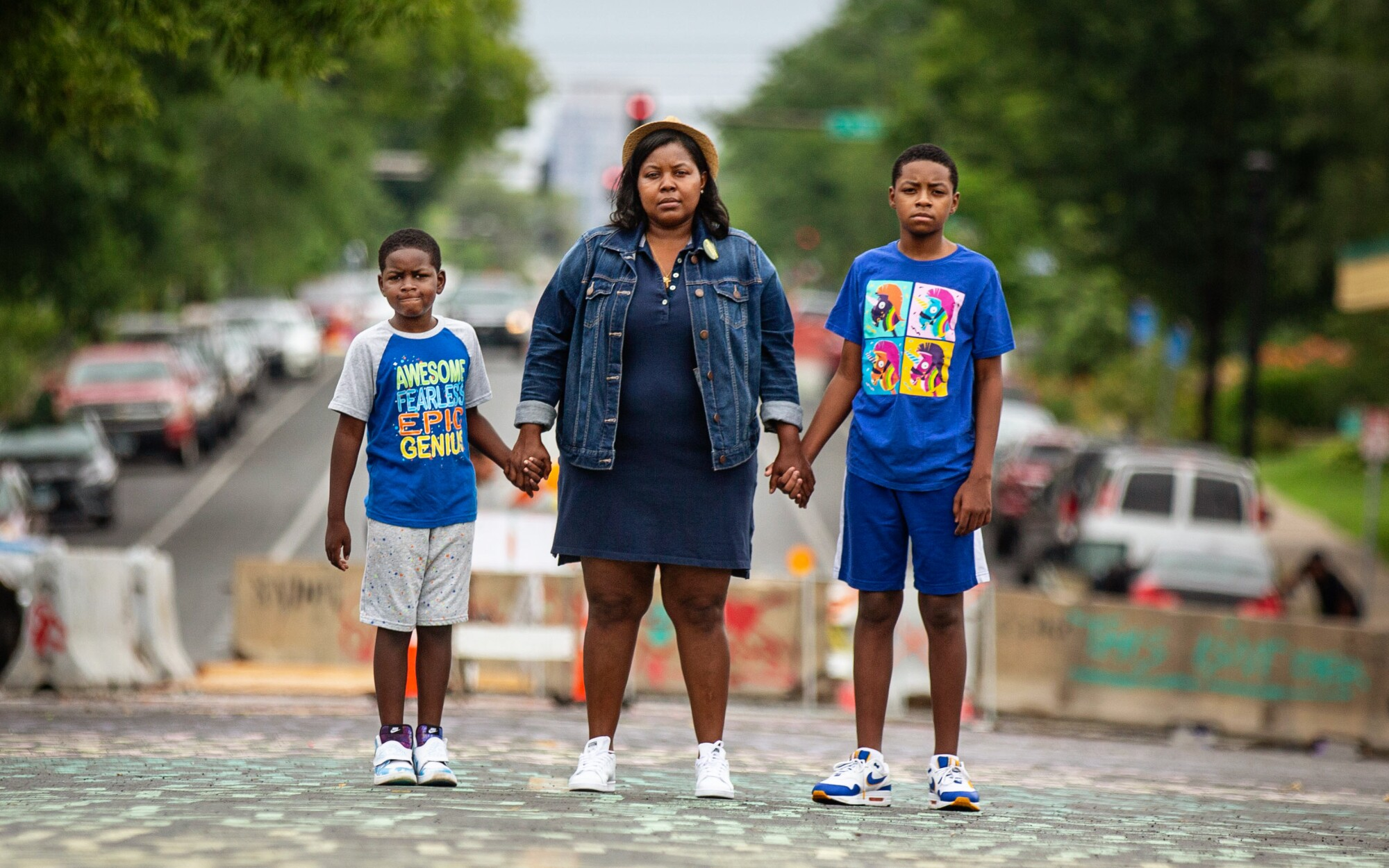 Alicia Smith and sons Alonzo, 7, left, and Walter III, 11, stand near where George Floyd was killed in South Minneapolis