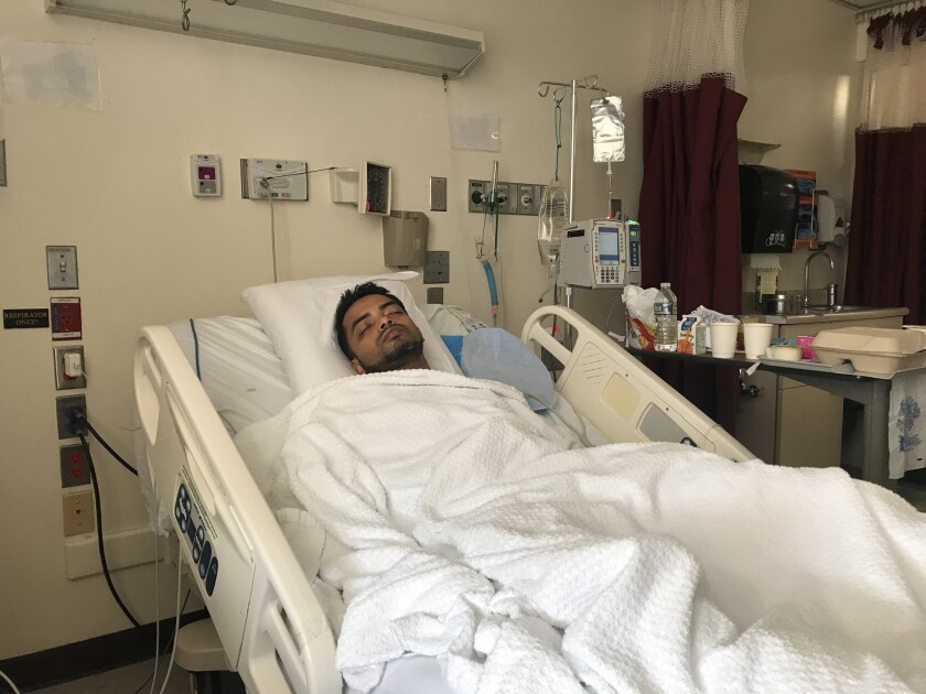 Muhammad Ahmed, pictured in his hospital bed on Monday, was shot when he chased down three robbers who grabbed $2,000 from a Queens grocery store on Saturday.