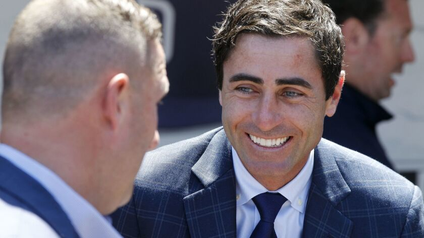 General Manager A.J. Preller, right, smiles during a conversation at the Padres dugout before Opening Day at Petco Park in San Diego on Thursday, March 29, 2018.