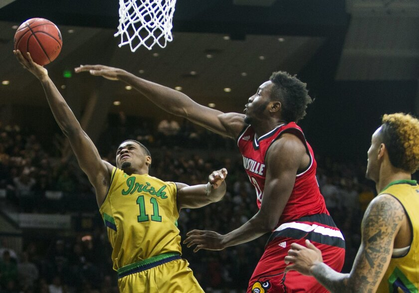 Notre Dame's Demetrius Jackson (11) goes in for a layup next to Louisville's Chinanu Onuaku (32) during the second half of Notre Dame's 71-66 win in an NCAA college basketball game Saturday, Feb. 13, 2016, in South Bend, Ind. (AP Photo/Robert Franklin)