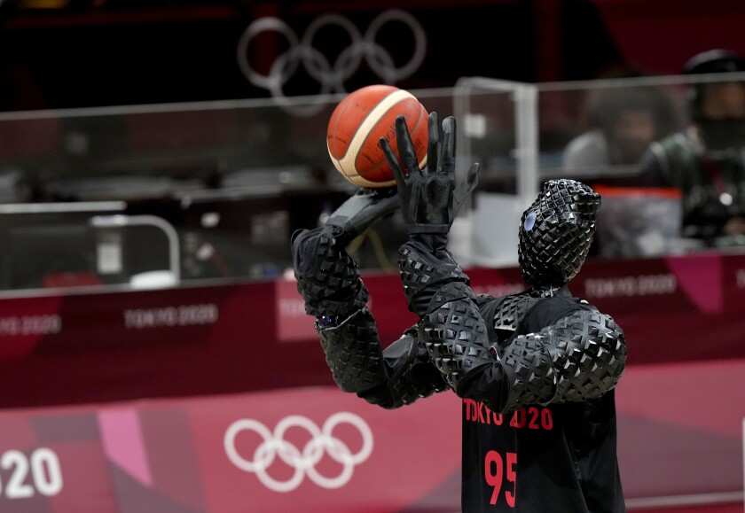 A robot in a basketball jersey stands poised to shoot a basketball.