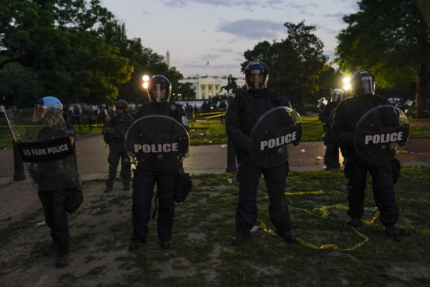 Police in riot gear stand in front of the White House on Saturday May 30.