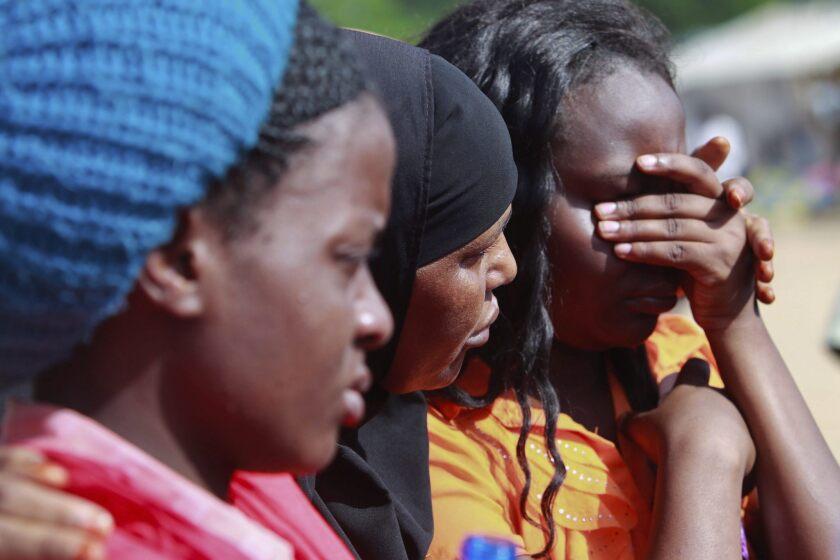 Supervivientes del ataque contra la Universidad de Garissa se consuelan mutuamente en el campamento militar de Garissa (Kenia), hoy, viernes 3 de abril de 2015. Al menos 147 personas perdieron la vida y más de 79 resultaron heridas ayer cuando terroristas del grupo yihadista somalí Al Shabab se hicieron pasar por fieles que iban a rezar en la mezquita del campus para atacar el centro y tomar como rehenes durante más de 16 horas a un grupo indeterminado de estudiantes y profesores. Los atacantes detonaron varios artefactos explosivos y dispararon de manera indiscriminada contra los presentes hasta lograr atrincherarse en una de las residencias donde se alojan los universitarios. Las Fuerzas de Defensa de Kenia consiguieron evacuar tres de las cuatro residencias y abatieron a tiros a cuatro de los atacantes, mientras que otro terrorista fue detenido cuando intentaba escapar de la zona, informó el Ministerio del Interior.