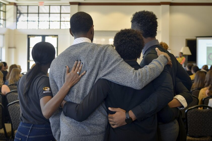 In this Saturday, Nov. 7, 2015, photo, members of the anti-racism and black awareness group Concerned Student 1950 embrace during a protest in the Reynolds Alumni Center on the University of Missouri campus in Columbia, Mo. Some campus groups have been protesting the way university president Tim Wo
