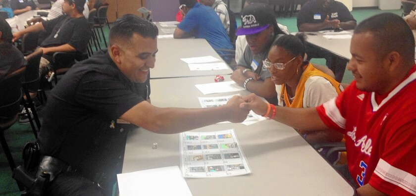 Officer Paul Sandate of the 77th Street Division congratulates Edgar Garcia for getting the correct answer in a game about law enforcement procedure during an exercise for people with autism.