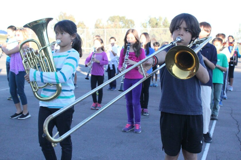 Mission Bay Montessori Academy band student Emiliano Casanova, pictured at right, stands in formation while playing his trombone during a Nov. 19 rehearsal in University City for the upcoming La Jolla Christmas Parade.