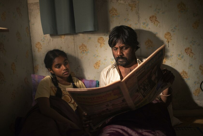 "Jesuthasan Antonythasan (Dheepan) and Claudine Vinasithamby (Illayaal) read the paper in ""Dheepan."""