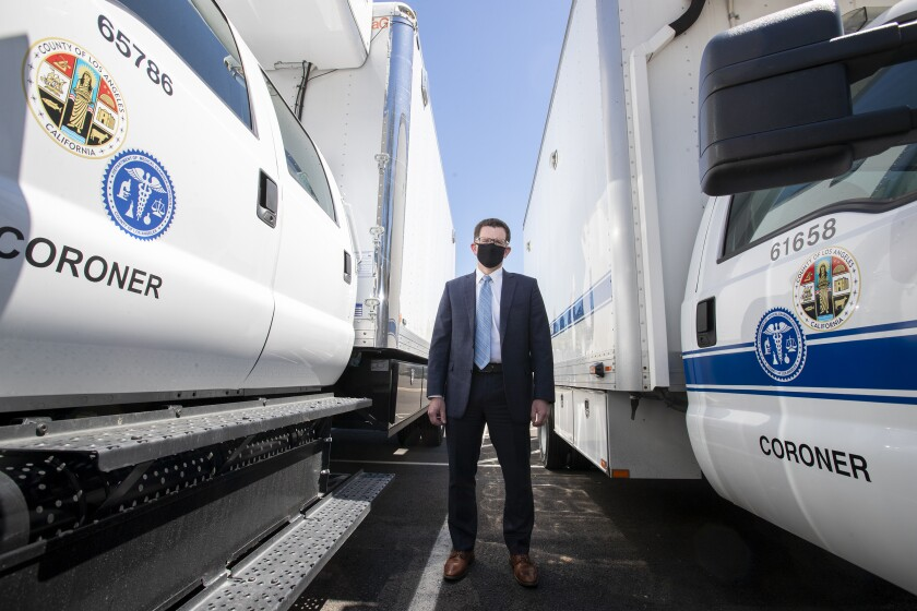 Los Angeles County Chief Medical Examiner Jonathan Lucas stands between large refrigerated trucks used to transport the dead. The coroner's office has tripled its storage space to 1,500 to be ready for a possible COVID-19 surge.