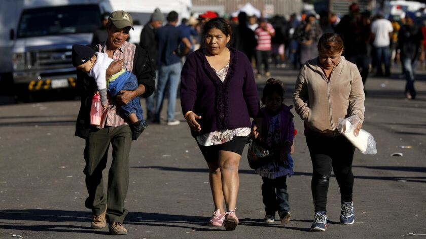 A Honduran family walks near the Benito Juarez Sports Center one block from the border in Tijuana on Nov. 26.