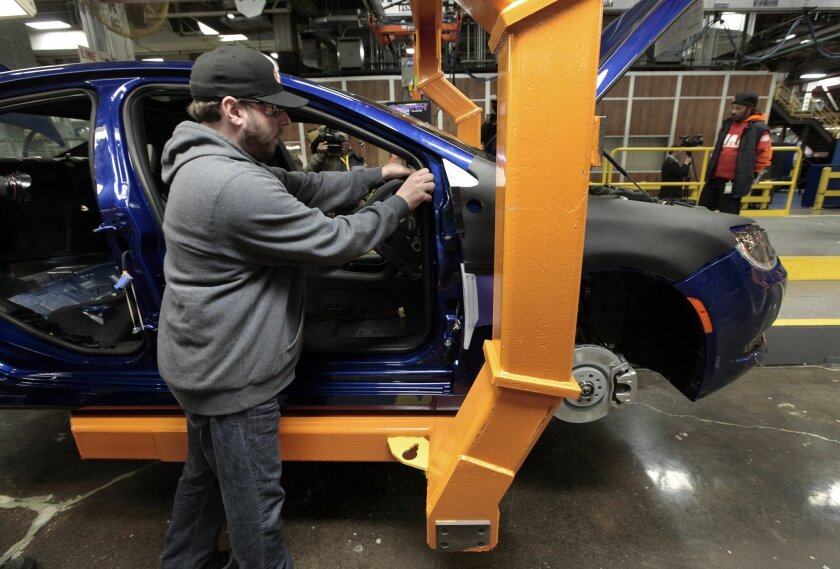 In this March 14, 2014 photo, an assembly line worker builds a 2015 Chrysler 200 automobile at the Sterling Heights Assembly Plant in Sterling Heights, Mich. The U.S. trade deficit fell in July to its lowest level since January, as exports of autos, telecom equipment, industrial machines and semiconductors rose, the Commerce Department reported Thursday, Sept. 4, 2014. (AP Photo/Paul Sancya)