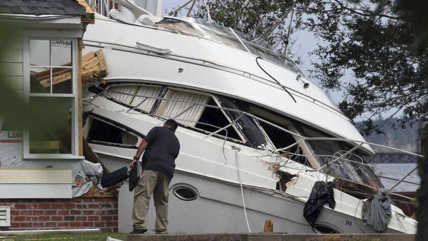An insurance adjuster looks over a storm beached yacht off of East Front Street in New Bern, N.C., T